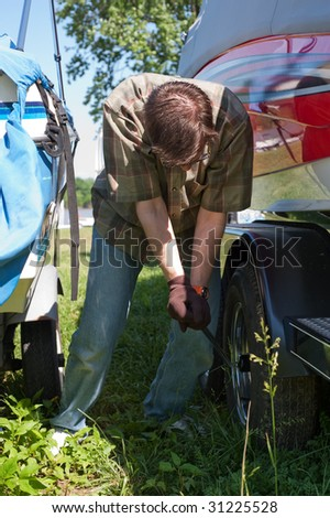 A man is tightening the lug nuts on a boat trailer wheel for safety in traveling. - stock photo