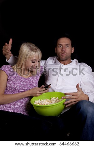 a man is upset that his girlfriend is texting while she shoud be watching a movie with him.