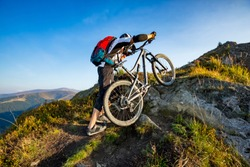 A man is walking up the hill with enduro bicycle, on the rock trail. Background of mountains and blue sky. Beautiful summer day. Mountain bike race.