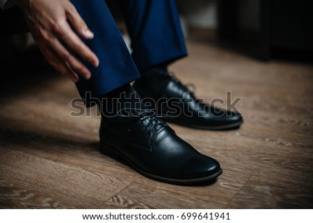 A man is wearing black shoes in close-up.