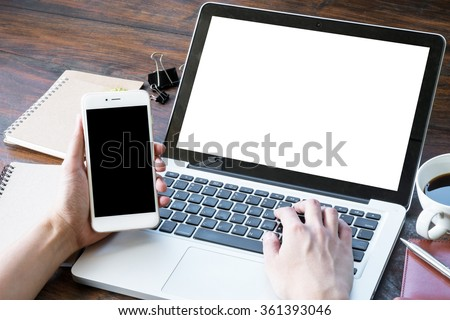 A man is working by using a laptop computer and a smartphone on vintage wooden table.  #361393046