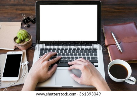 A man is working by using a laptop computer on vintage wooden table. Hand typing on a keyboard. Front view.