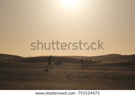 A man jogs or runs through a dry barren desert landscape with sand dunes, under a blaring hot sun. With room for text.