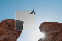 a man jumping out of monochrome frame crossing cliff. Positive thinking and out of the box concept