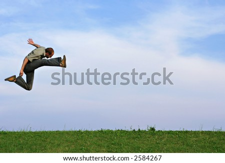 A man jumping very high over a grassy hill against a blue sky