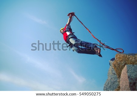 A man jumps from a cliff into the abyss. #549050275