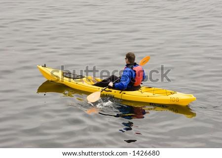 A man kayaks on the ocean