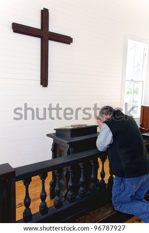 A man kneeling and praying at a church in front of a wooden cross.