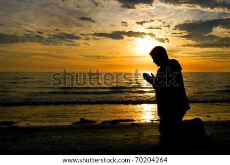 A man kneeling and praying at the ocean with his head bowed.