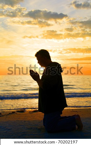 A man kneeling and praying at the ocean with the sun framing his head.