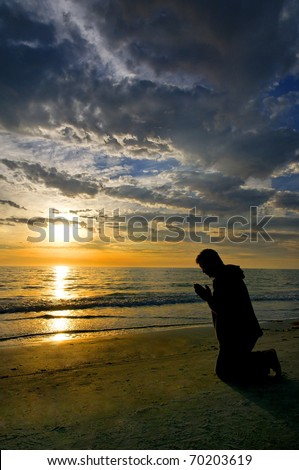A man kneeling and praying on the beach with dramatic clouds and a golden sunset.
