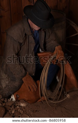 A man kneeling down by a wine barrel looking for something.