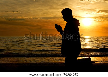 A man kneeling on the beach and praying in front of a golden sunset.