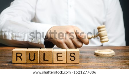 A man knocks a hammer publishes new rules and laws. Setting clear rule and restrictions. Leadership and discipline. Authoritarianism, tight control framework. Norms and laws in society, state Photo stock ©