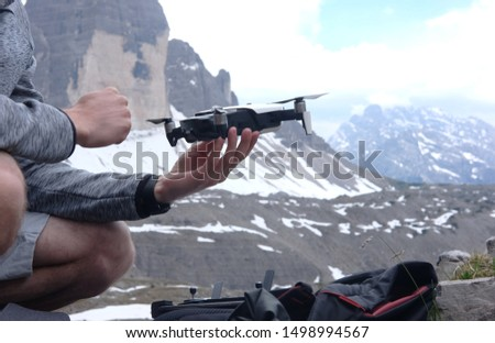 a man launches in his hands a doron for video shooting in the mountains against the background of a mountain landscape, the theme of active leisure, hobbies and videos  #1498994567
