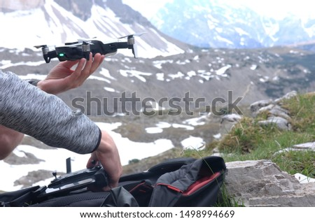 a man launches in his hands a doron for video shooting in the mountains against the background of a mountain landscape, the theme of active leisure, hobbies and videos  #1498994669