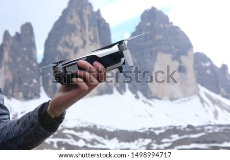 a man launches in his hands a doron for video shooting in the mountains against the background of a mountain landscape, the theme of active leisure, hobbies and videos  #1498994717