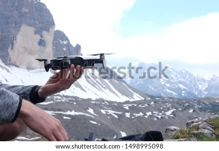 a man launches in his hands a doron for video shooting in the mountains against the background of a mountain landscape, the theme of active leisure, hobbies and videos  #1498995098
