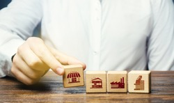 A man lays in a row blocks with symbols of business shops, offices and factories. Building a successful business empire. Investments. Merge small competitors, expansion. Franchise concept.