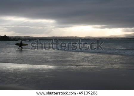 a man leaves the sea after a surf as the day comes to a dramatic end in byron bay australia