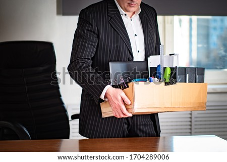 A man leaves the workplace with a cardboard box in his hands. Job change. The transition to another job. Dismissal. Changing the type of activity. Search for the best features. Stock photo ©