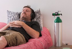 A man lies on his bed while breaths through a cannula connected to an oxygen cylinder