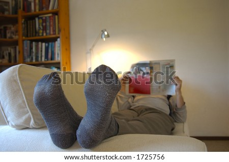 A man lies on the couch with his feet up, reading the paper. Focus on the slightly worn socks. Space for text on the wall, top right.
