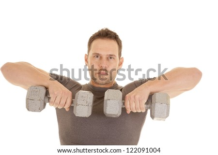 A man lifting weights working out his shoulders with a serious expression on his face.