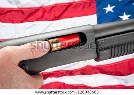 A man loads a shotgun shell into a pump action shotgun.  Shot against an American flag.