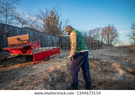 A man loads sand with a shovel into the trailer of the walk-behind tractor, for delivery to the cottage #1344673154