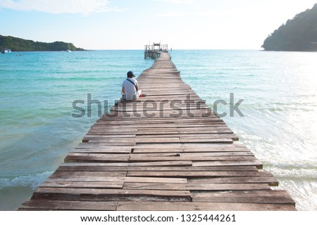 A man lonely sitting on the wooden pier at the sea