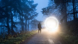 A man looking at a mysterious glowing portal  on a forest road on a foggy winter evening.