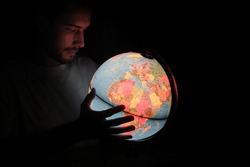 a man looking at a Rotating World Globe Earth Lamp light Illuminated Desk Map Geography in the dark night with it face illuminated