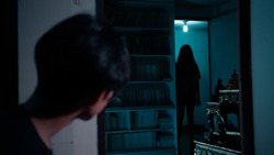 A man looking at scariest Thai lady ghost across the room staring at him.The lady ghost is completely in silhouette.