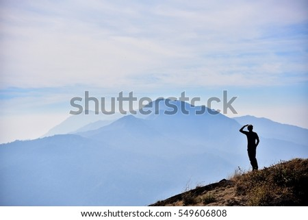 A man looking at the other hill.