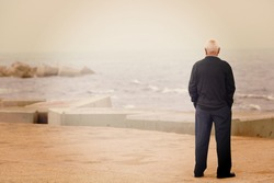 A man looking at the sea on the dock. Image has a vintage effect.