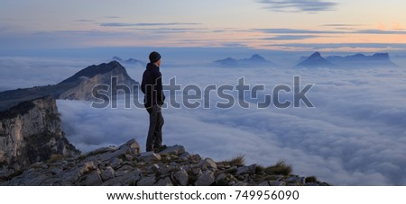 A man looking over a sea of clouds in the mountains at dawn.