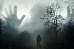 A man looking up at a huge ghostly hooded figure appearing out the mist. On a moody winters day in the countryside. With a grunge, vintage edit.