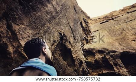 A man looking up at the treacherous cliffs above.