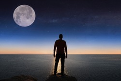 A man looks at the stars and the moon.  Elements of this image furnished by NASA.