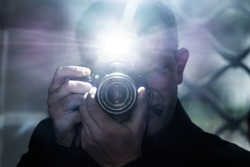 a man looks into the camera's viewfinder and takes pictures using a flash, a photographer on the background of a metal grating, a selfie in a gloomy room