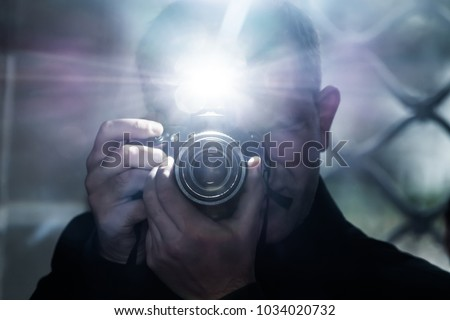 Photo of  a man looks into the camera's viewfinder and takes pictures using a flash, a photographer on the background of a metal grating, a selfie in a gloomy room