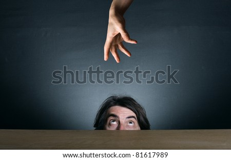 A man looks out from behind his desk, hiding the hand that reaches out to him from above.