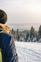 A man looks over the top of the mountain forest. Hiker in ski suit looks at tall snowy fir trees covered with snow in the forest mountains landscape. Winter holiday and recreation, winter resort