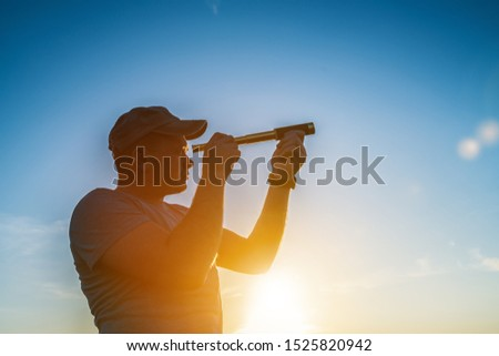 A man looks through a spyglass against a sunset. Tourism and travel. Business concept look into the future, peep