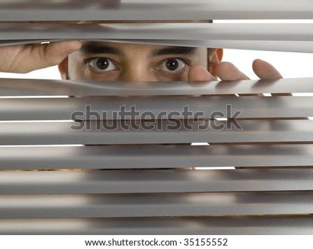 A man looks to the camera through the blinds. - stock photo
