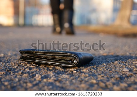 A man lose black wallet on the road. Losing wallet concept.