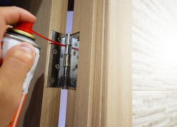 A man lubricates door hinges with oil.