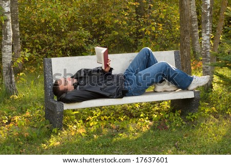 A man lying on a bench reading a book