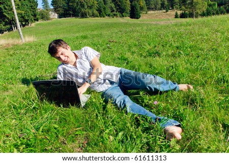 A man lying on the grass taking a break from his work.